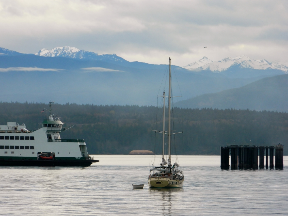 A Washington State ferry comes in to dock in Port Townsend with the Olympic Mountains in the background.