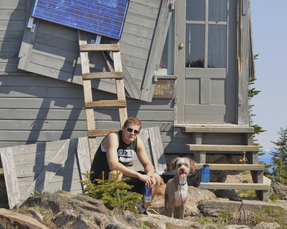 My co-worker, Thomas Kyle-Milward, and my dog, Ms. Molly, relax in the beautiful May weather. The fire lookout was built in 1932 or 1933 and was placed on the National Historical Register in 1987. (Photo by Craig Craker)