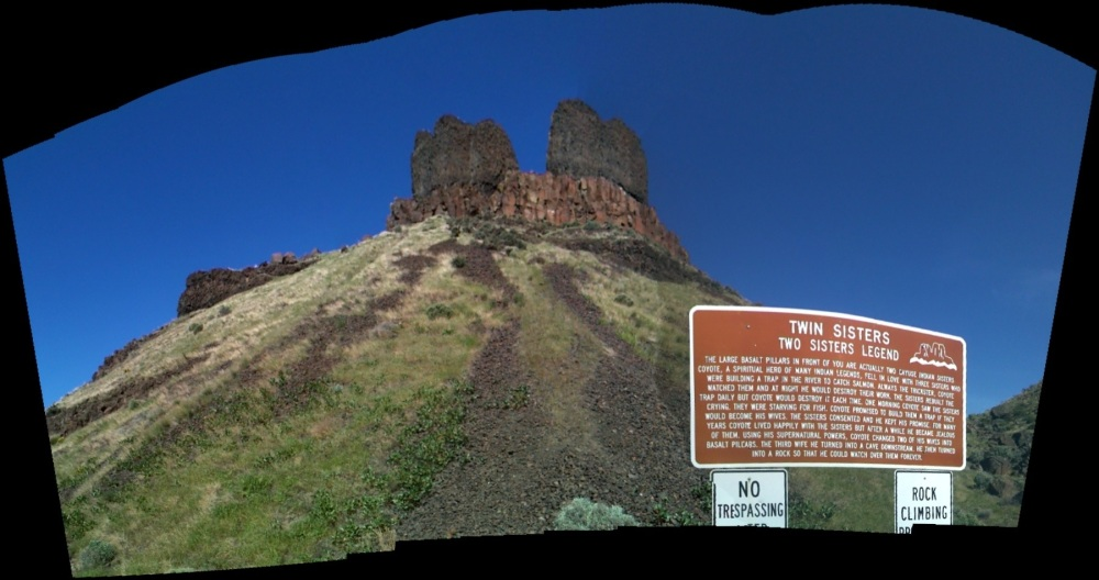 "An iPhone panorama of the Twin Sisters from the parking lot at their base, including the sign with the Native American legend on it. The no trespassing sign that is cut off says, ""No trespassing after dark."""