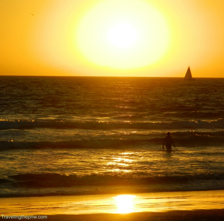 I was shooting photos of the sun going down with the sail boat in the background, and I got lucky with the man walking out of the surf in this shot.