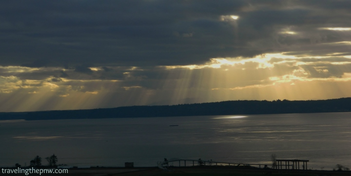 A sunspot appears over Chambers Bay, with the bridge to the beach in the foreground.