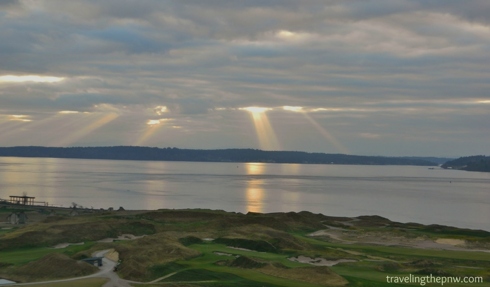 Sun rays pour over the Puget Sound with the Chambers Bay Golf Course in the foreground.