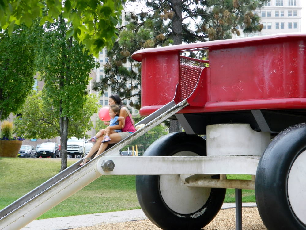 Catarina and Veronica cruise down the slide on the giant Radio Flyer wagon at Riverfront Park.