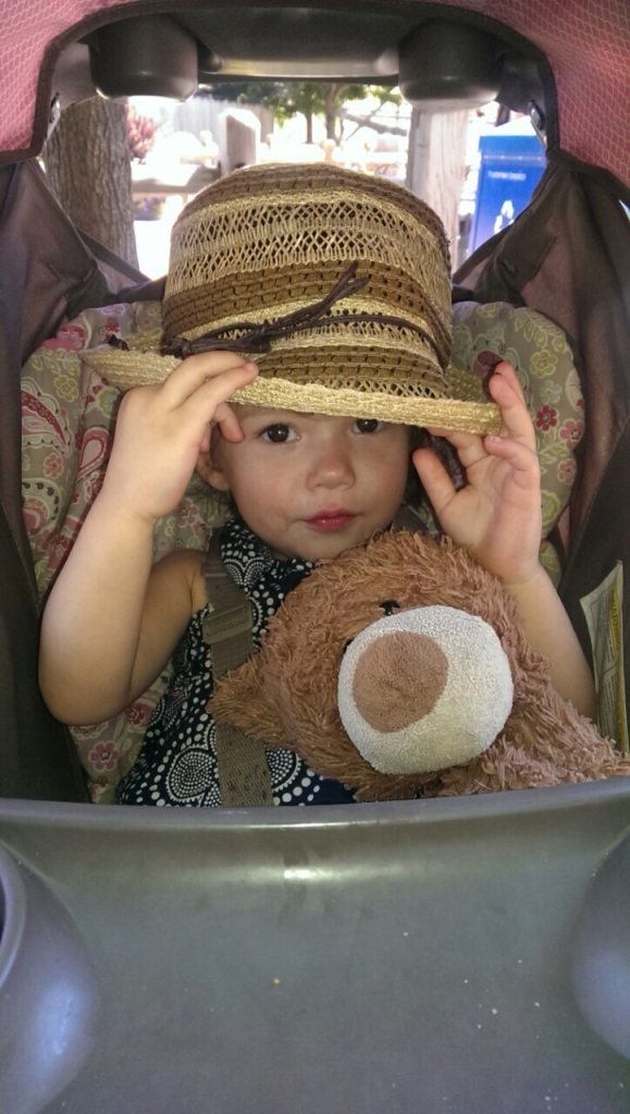 Catarina rocking her Grandma Robbie's hat on a hot day at the amusement park.