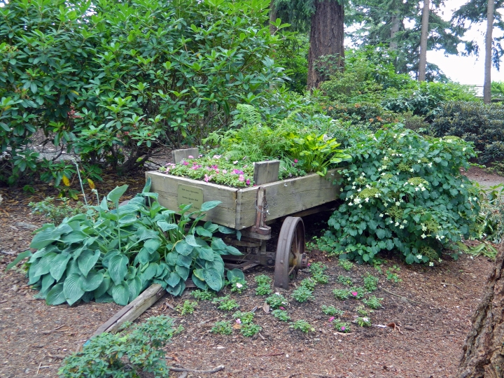 This cool old school wagon is adorned with colorful flowers in the middle of the park.