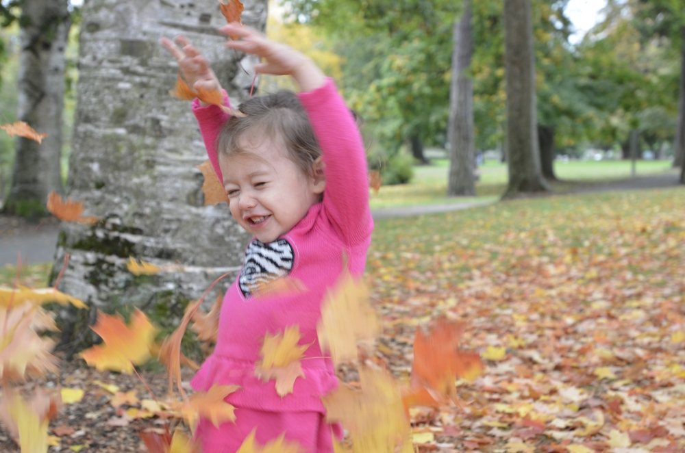 Catarina loves playing in leaves, and there are a lot in Wright Park.