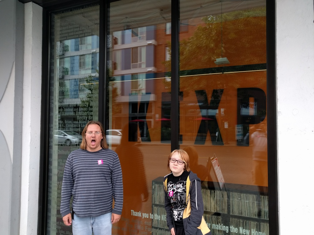 Chris Gove and his daughter, Gianna, pose in front of radio station KEXP's vinyl library.